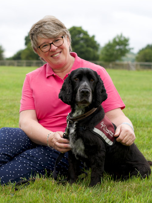 Sue and her hearing dog kristo sitting on grass