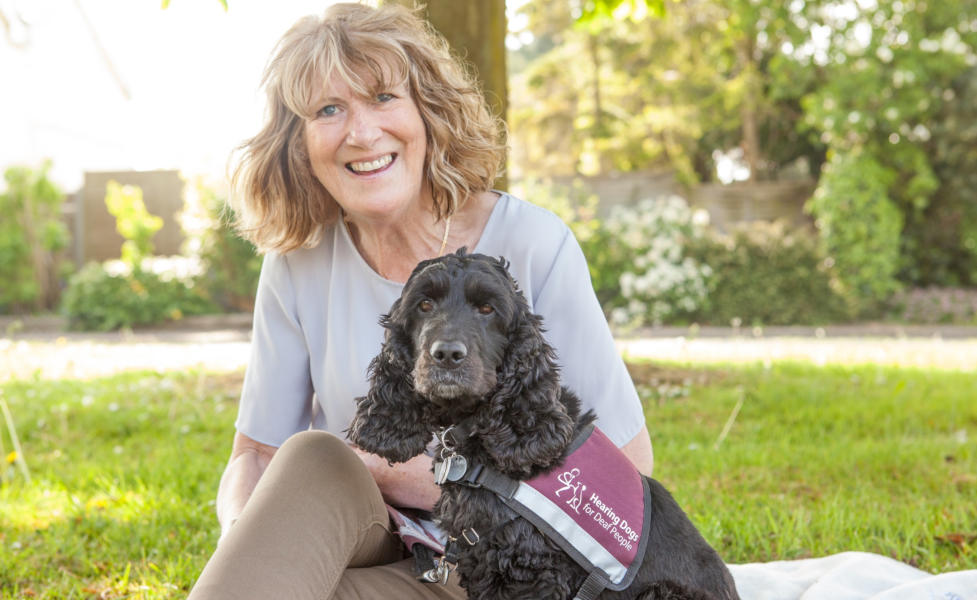 Geraldine with her Hearing Dog Bella sitting on a grassy area