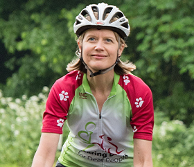 a woman wearing a cycling helmet and hearing dogs cycling livery
