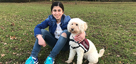 Sarah sitting down with hearing dog Waffle