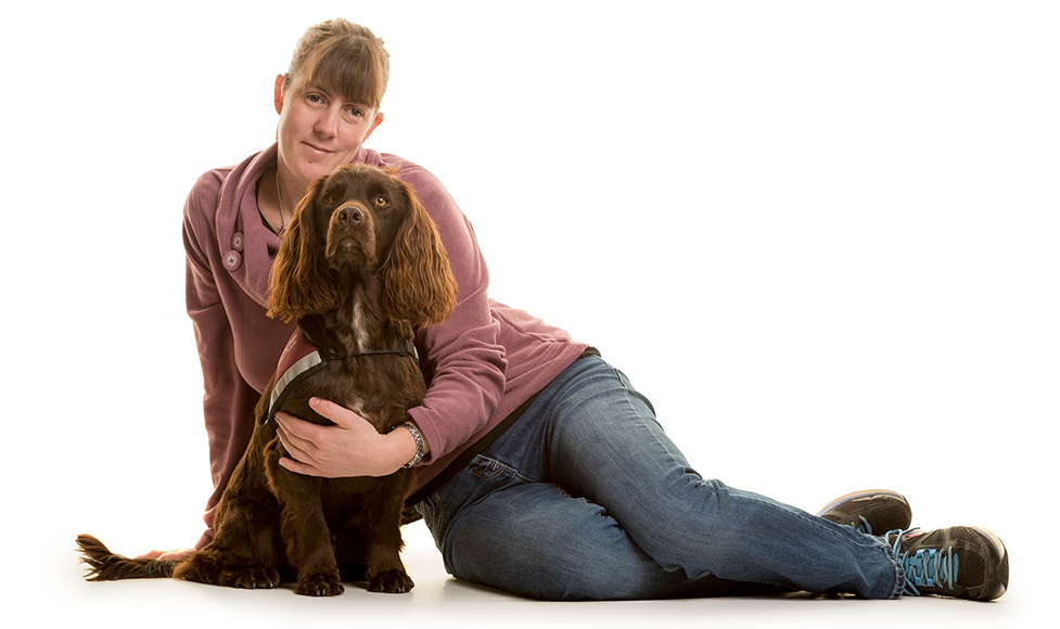 Jen sitting on the floor, with her arm around cocker spaniel hearing dog Dram, who is sitting in front of her