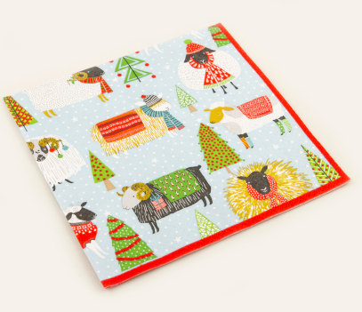 Napkins with a full colour printed design featuring hat and scarf wearing sheep and goats with Christmas trees interspersed