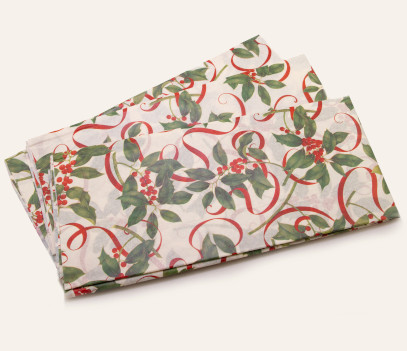 tissue paper with a green holly leaf and red berry design and red ribbons entwined throughout