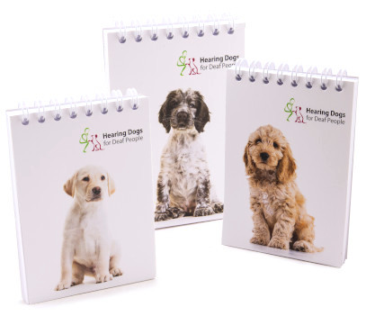 Three spiral bound notepads with hearing dogs images on the front