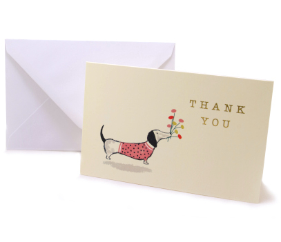 "cream coloured card with a design of a dachshund wearing a pink black spotted jumper holding flowers in its mouth. The text ""thank you"" is printed in yellow lettering"