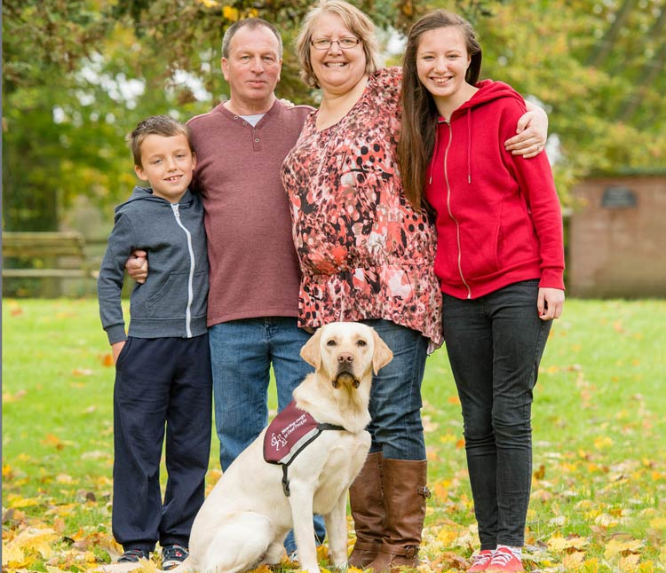 Labrador hearing dog with deaf person and family